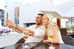 采取与片剂个人计算机的愉快的夫妇selfie在咖啡馆 免版税库存照片
