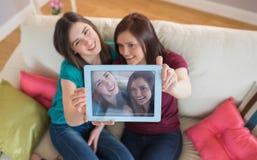 采取与片剂个人计算机的长沙发的两个微笑的朋友一selfie 库存图片