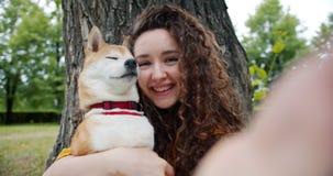 采取与狗的愉快的女孩画象selfie在拥抱宠物藏品照相机的公园 影视素材