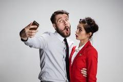 采取与电话照相机的两个同事朋友selfie 免版税库存照片