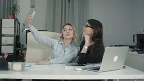 采取与电话的两个女性同事selfie在办公室 免版税库存照片