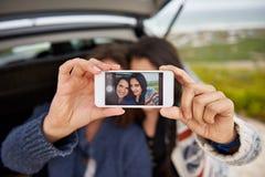 采取与电话的女性朋友一selfie 库存图片