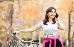 采取与电话的妇女,当乘驾自行车时 免版税图库摄影