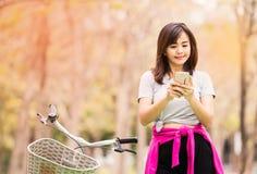 采取与电话的妇女,当在乡下路时的乘驾自行车 免版税库存照片
