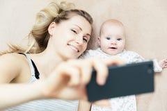 采取与电话的母亲和小婴儿婴孩selfie 库存图片