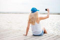 采取与电话的年轻白肤金发的女孩selfie在木码头 库存图片