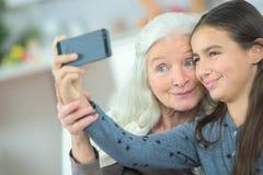 采取与祖母的小女孩selfie 免版税库存照片
