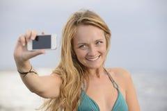 采取与移动电话的妇女照片在海滩 免版税图库摄影