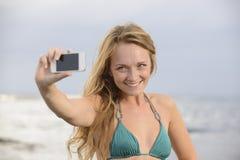 采取与移动电话的妇女照片在海滩 图库摄影