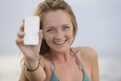采取与移动电话的妇女照片在海滩 免版税库存照片