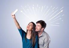 采取与箭头的逗人喜爱的夫妇selfie 免版税库存照片