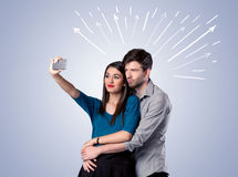 采取与箭头的逗人喜爱的夫妇selfie 免版税图库摄影