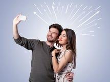 采取与箭头的逗人喜爱的夫妇selfie 库存照片