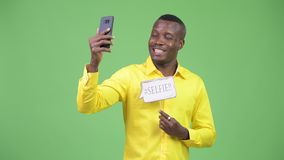 采取与纸标志的年轻愉快的非洲商人selfie 股票视频