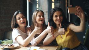采取与翘拇指姿态的愉快的少女selfie在咖啡馆笑 股票录像