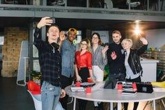 采取与行家小组的微笑的年轻白种人商人一selfie工友在办公室在工作的之前或之后 免版税库存照片