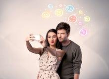 采取与面带笑容的愉快的夫妇selfie 免版税库存图片