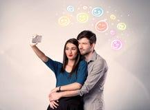 采取与面带笑容的愉快的夫妇selfie 免版税库存照片