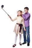采取与selfiestick的男孩和女孩selfies  免版税图库摄影