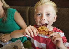采取乳酪薄饼的大叮咬逗人喜爱的小男孩在餐馆 免版税库存图片