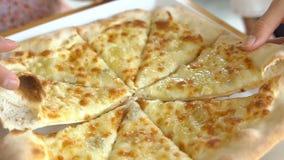 采取乳酪薄饼的手从小板材切开 影视素材