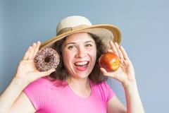 采取五颜六色的油炸圈饼的秀丽女孩 有甜点的滑稽的快乐的妇女,点心 饮食,节食的概念 速食 免版税库存图片
