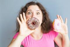 采取五颜六色的油炸圈饼的秀丽女孩 有甜点的滑稽的快乐的妇女,点心 饮食,节食的概念 速食 库存图片