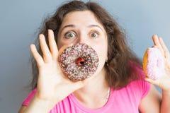 采取五颜六色的油炸圈饼的秀丽女孩 有甜点的滑稽的快乐的妇女,点心 饮食,节食的概念 速食 库存照片