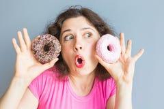 采取五颜六色的油炸圈饼的秀丽女孩 有甜点的滑稽的快乐的妇女,点心 饮食,节食的概念 速食 图库摄影