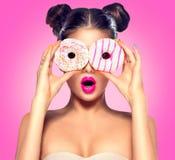 采取五颜六色的油炸圈饼的秀丽式样女孩 免版税库存照片
