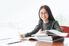 采取从书的女学生笔记在图书馆,坐在桌上的年轻亚裔妇女做任务在大学图书馆里 库存照片