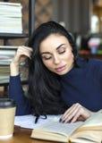 采取从书的女学生笔记在图书馆 坐在桌上的年轻亚裔妇女做任务在学院 库存照片