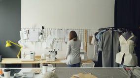 采取从剪裁书桌和垂悬的后面观点的创造性的女性裁缝他们的剪影在墙壁上面桌上 计划 股票录像