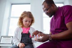 采取从宜人的儿科医生的逗人喜爱的矮小的卷曲女孩药片 库存照片