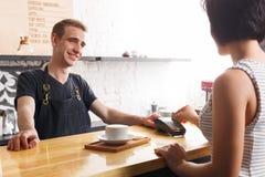 采取从客户的微笑的男服务员付款在咖啡店的柜台 图库摄影