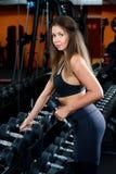 采取从杠铃行的好女孩哑铃在健身房的 免版税图库摄影