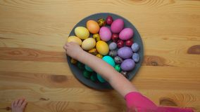 采取从板材的儿童的手多彩多姿的复活节彩蛋 股票视频