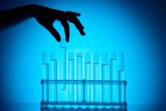 采取从立场的化学家玻璃管在蓝色 免版税库存图片