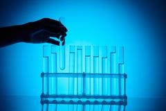 采取从立场的女性化学家玻璃管在蓝色 免版税库存照片