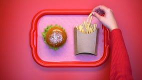 采取从纸盒箱子的女性手嘎吱咬嚼的薯条在盘子,肥腻快餐 免版税库存照片