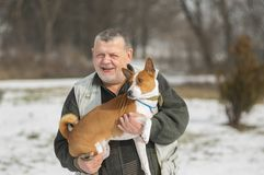 采取他可爱的basenji狗的白种人老人室外画象  图库摄影
