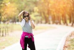 采取休息的亚洲行政成熟妇女赛跑者 库存照片