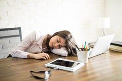采取休息的拉丁妇女在她的办公室 免版税库存照片