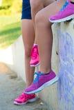 采取休息的疲乏的妇女赛跑者在艰苦跑以后在公园 免版税库存图片