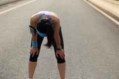 采取休息的疲乏的妇女赛跑者在艰苦跑以后 免版税库存图片