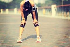 采取休息的疲乏的妇女赛跑者在艰苦跑以后 库存照片