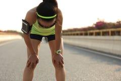采取休息的疲乏的妇女赛跑者在艰苦跑以后 库存图片