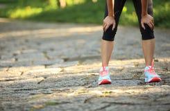 采取休息的疲乏的母赛跑者在跑以后 免版税库存图片