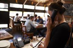 采取保留的少妇由电话在餐馆 免版税库存照片