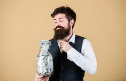 采取做的生意金钱 采取金钱的商人在玻璃瓶子外面 投入有胡子的人投资金钱  库存照片